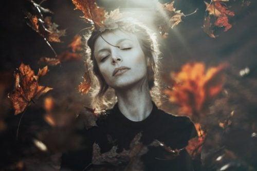Kvinde står i en skov med efterårs bladene omkring sig