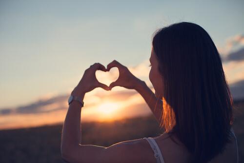 Kvinde laver hjerte med hænderne