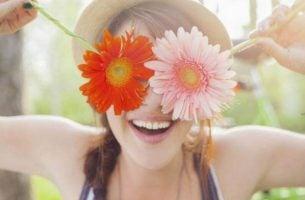 Smilende kvinde med blomster for øjnene opfordrer dig til at lære at elske dig selv