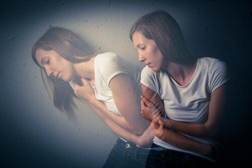 Kvinde med et spejlbillede af sig selv er stresset over chikane på arbejdspladsen