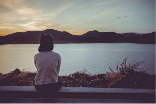 Kvinde sidder og kigger ud over en sø