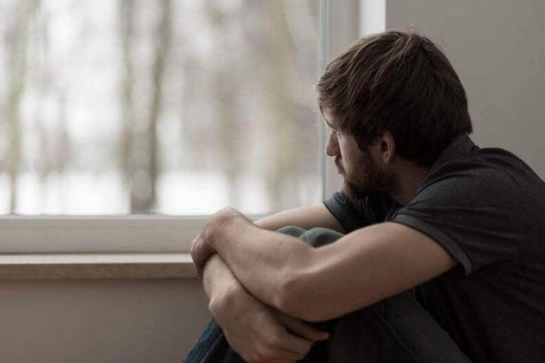 Trist mand ser ud af vindue og oplever ufrivillig ensomhed