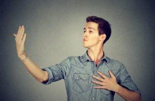 Mand kigger arrogant på sin hånd og illustrerer, hvordan man kan håndtere bedrevidende personer