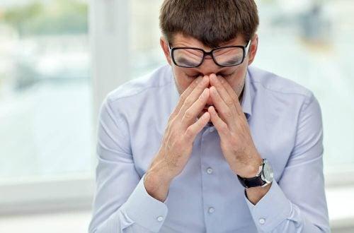 Mand tager sig til hoved og er frustreret over chikane på arbejdspladsen