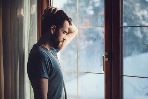 Mand står ved vindue og tænker