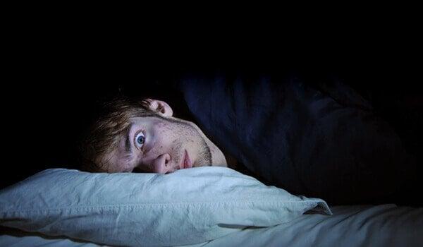Mand ligger vågen på grund af rastløse ben