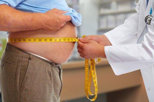 Læge måler overvægtig mands mave, da fedme kan være årsag til søvnapnø