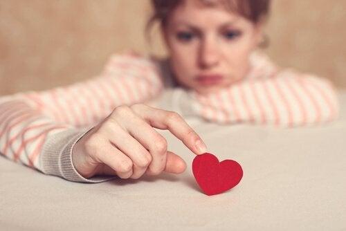 Pige med et papirhjerte er i tvivl omkring kærlighed