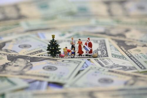 Små menneske figurer står på en masse penge. De vil bruge penge på oplevelser
