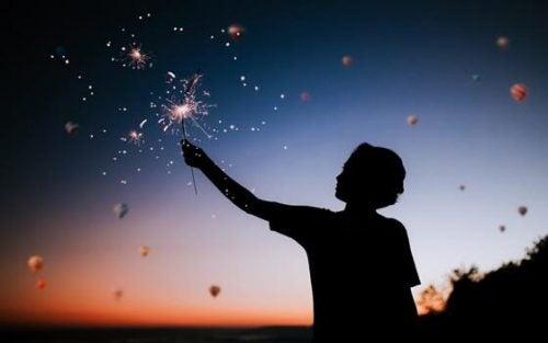 Dreng står med en stjernekaster op mod en klar nattehimmel. Brug penge på oplevelser