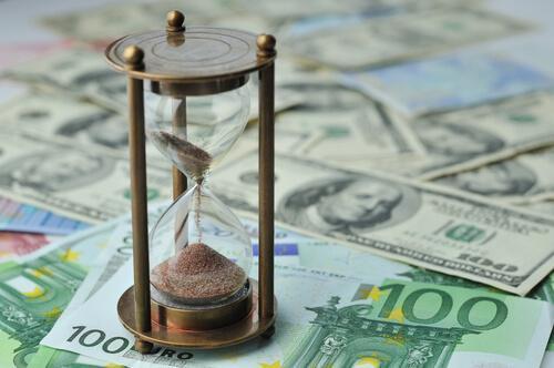 Timeglas står på en masse pengesedler. Brug dine penge på oplevelser