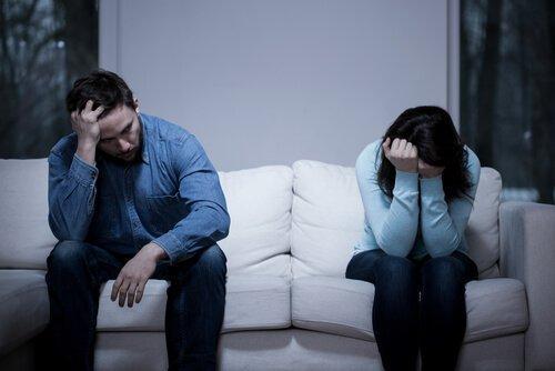 Trist par sidder i hver sin ende af sofaen og illustrerer situationen, når du skændes med din partner