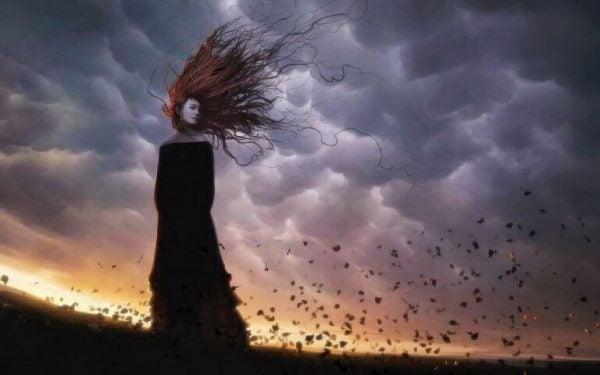 Kvinde i sort står i uvejr
