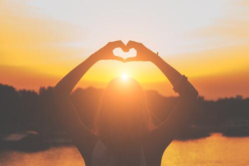 Kvinde laver hjerte med hænder foran sol