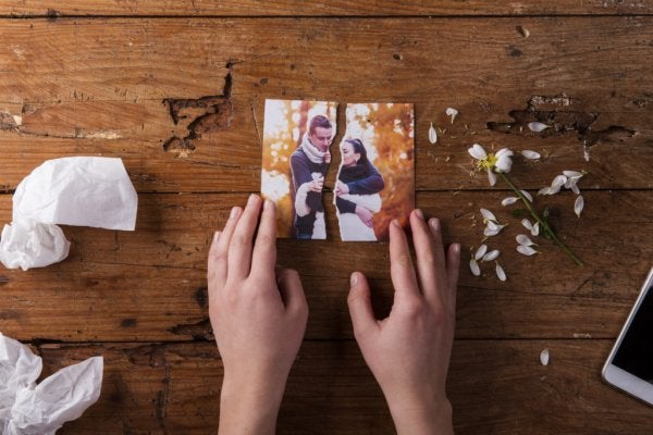 Hænder holder om ødelagt billede af par