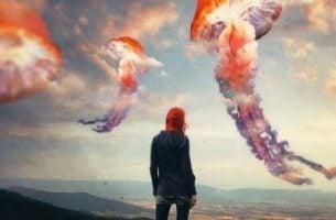 Person står overfor farverige skyer, der symboliserer lykke