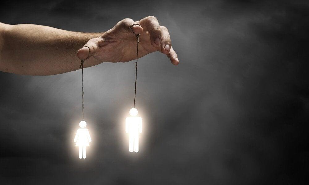 Hånd fører lysende dukker som symbol for at bruge andres svagheder