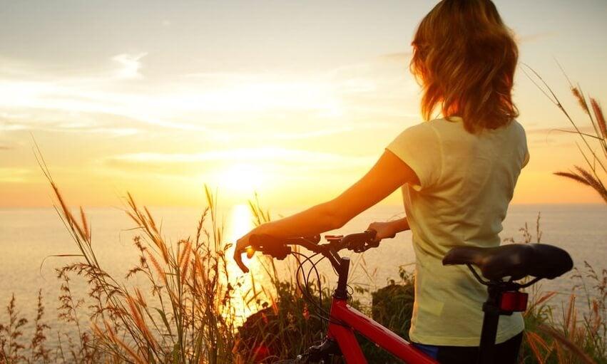 Kvinde med cykel foran solopgang