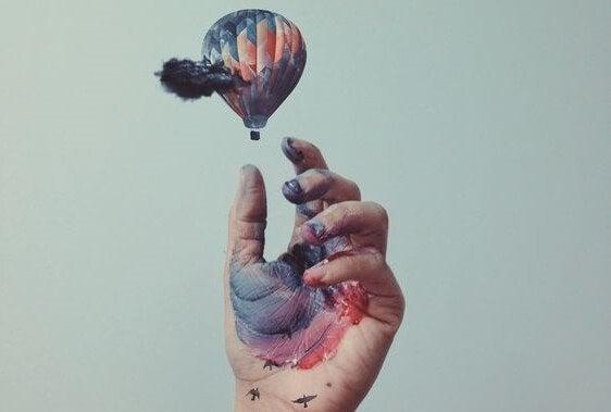Hånd med maling griber ud mod luftballon