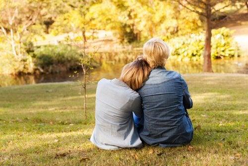 To personer krammer på græs foran sø