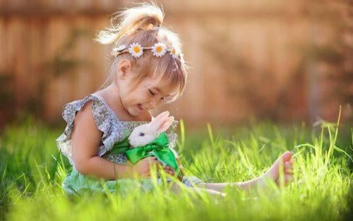 Pige sidder i græsset med kanin