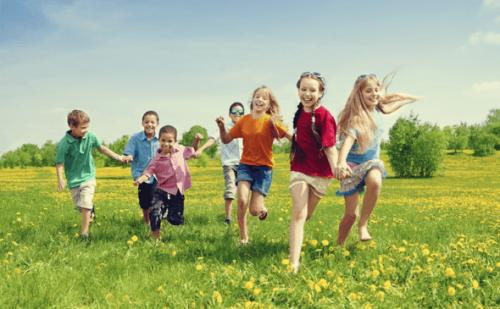 Børn løber på græsplæne