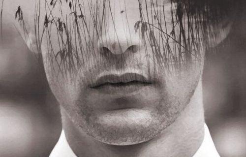 Mands ansigt i sort og hvid med siv foran