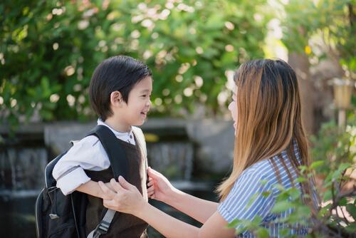 Dreng med skoletaske fortæller sin mor om den bedste første skoledag