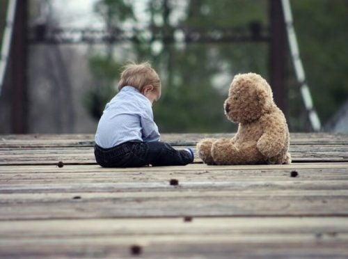 Dreng sidder med en stor bamse, at lære at sidde selv er en af de større milepæle i babys udvikling