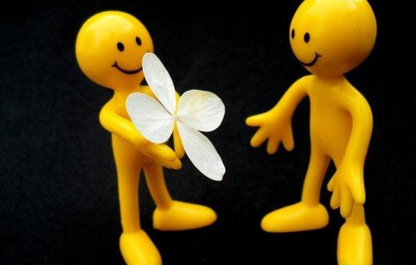 En dukke giver en blomst til en anden dukke