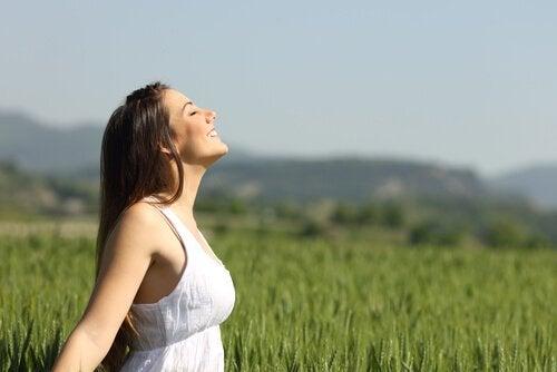 Kvinde laver beroligende vejrtrækningsøvelser i det fri