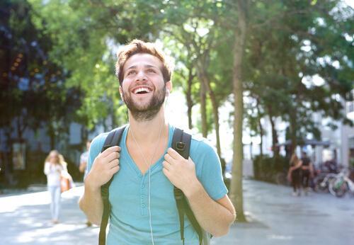 glad mand vandrer med rygsæk