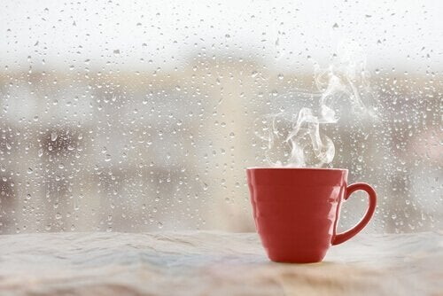 Kaffekop foran rude med regndråber på