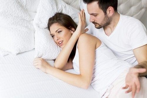 Kvinde, der afviser sin partner i en seng på grund af mangel på seksuel lyst