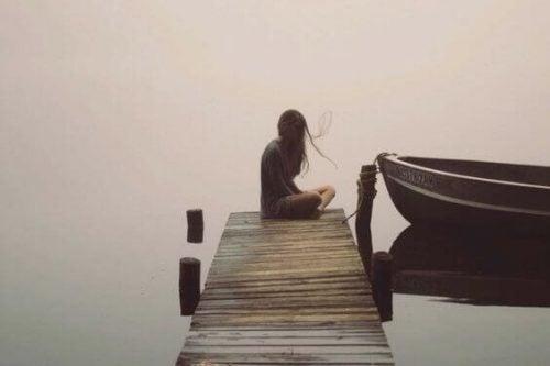 Kvinde sidder alene på bro