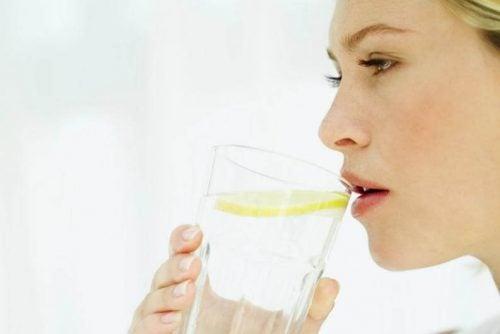 Kvinde drikker varmt vand med citron om morgenen
