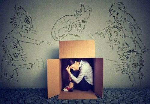 En kvinde, der gemmer sig i en papkasse