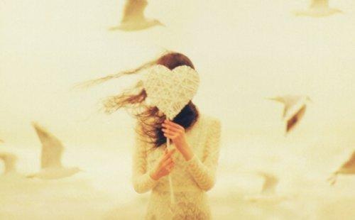 kvinder skjuler sig bag et hvidt hjerte