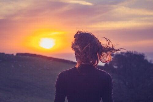 Kvinde kigger på solopgang og ønsker at overvinde fortiden