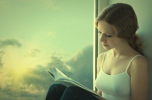 Kvinde ved vindue nyder fordele ved at læse