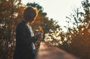 Kvinde med blomst er i færd med at tænke for meget på minder