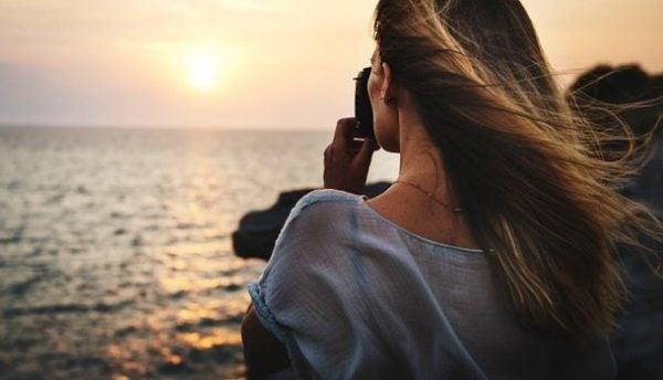 Kvinde tager billede ud over havet