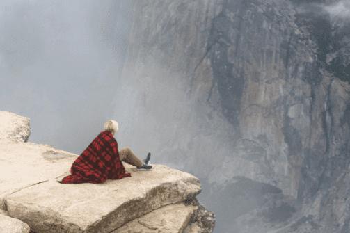 Kvinde der sidder på en sten højt oppe for at overfinde en fobi for højder