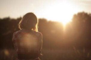 Kvinde ser på solen og nyder følelsesmæssig balance