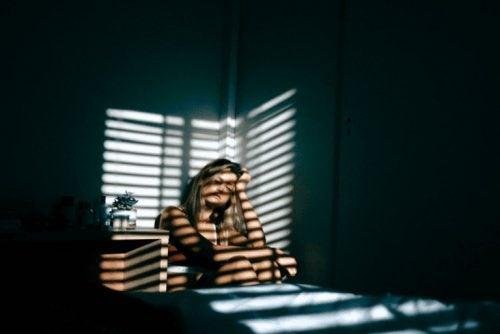 Kvinde, der sidder i hjoernet i mørke