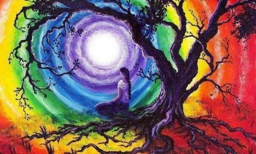 Kvinde sidder under træ foran stor regnbue