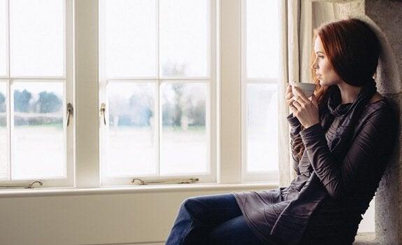 Kvinde drikker kaffe og ser ud af vindue