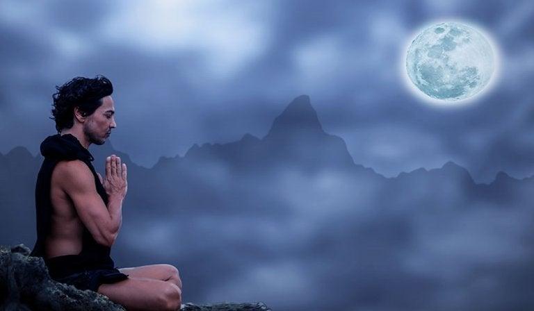 Mand mediterer ved fuldmåne og mærker, hvordan månen påvirker vores følelser