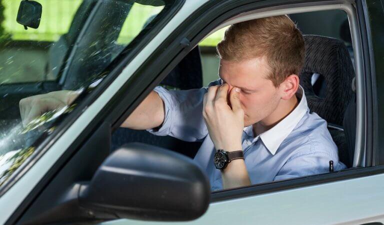 Mand sidder i sin bil og har hovedpine