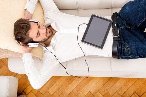 En mand, der nyder noget musik på sofaen